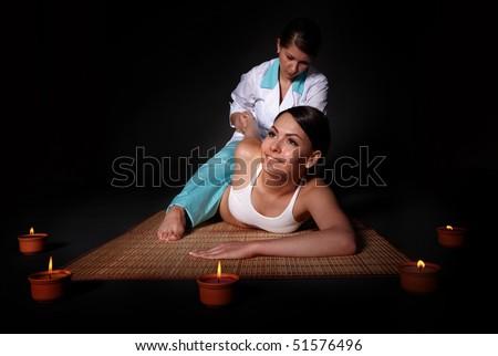 Beautiful white girl having thai massage. - stock photo