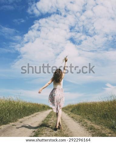 Beautiful white girl walking the road - stock photo