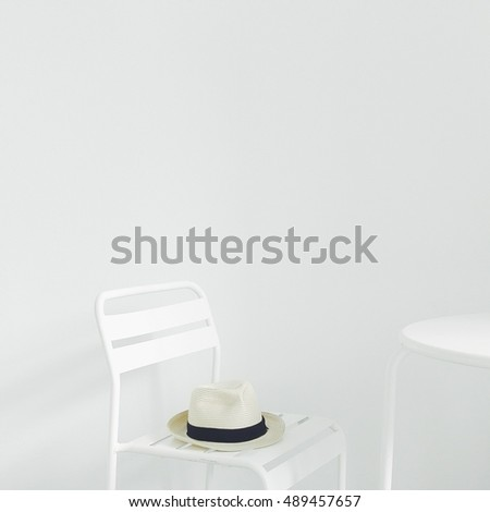 Beautiful white hat on chair. Summer hat on white chair. White background.