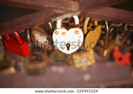 beautiful white heart-shaped padlock locked on iron chain, romance concept - stock photo
