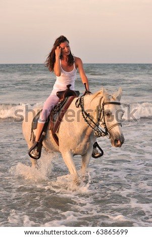 beautiful white horse in the sea and beautiful woman