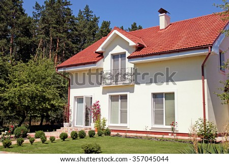 Beautiful white house in garden with green lawn and blue sky - stock photo