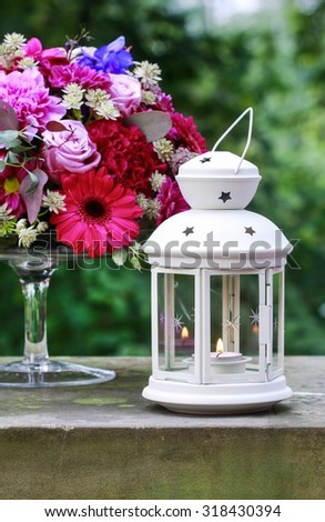 Beautiful white lantern and bouquet of flowers - stock photo