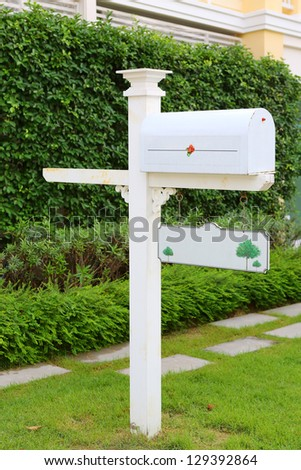 Beautiful white letter box in the garden - stock photo