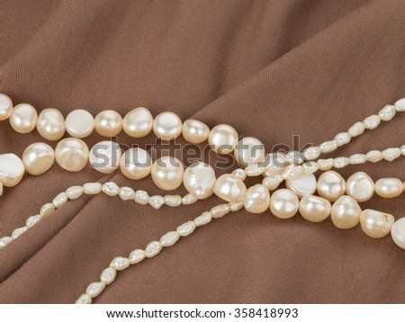Beautiful white lustrous necklace of natural pearls on brown fabric with pleats