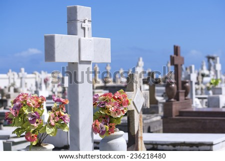 Beautiful white marble cross and flowers among many other crosses and grave markers at cemetery in Old San Juan, Puerto Rico - stock photo