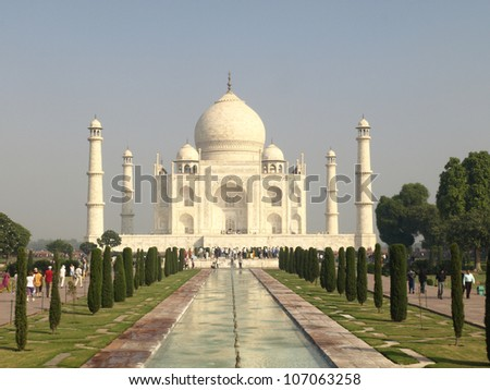 Beautiful white marble of the Taj Mahal seen from entrance gate - stock photo