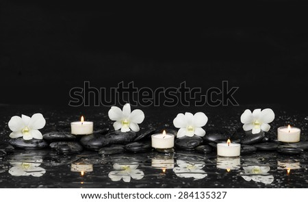 Beautiful white orchid with candle and therapy stones