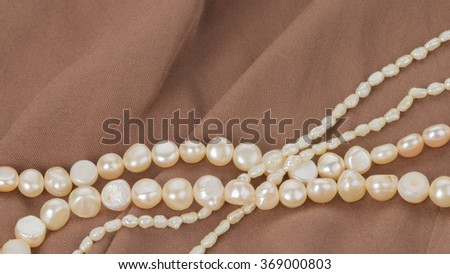 beautiful white pearl beads on brown fabric with pleats