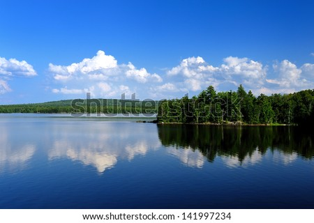 Beautiful white puffy clouds reflected on a cold Maine lake surrounded by Pine trees - stock photo