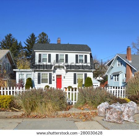 Beautiful White Red Door Suburban Home Clear Blue Sky Autumn Day White Picket Fence residential neighborhood USA - stock photo