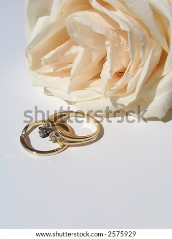 Beautiful white rose with dew drops and engagement ring over white background .Perfect image for event projects : marriage proposal , anniversary and Valentine's day .