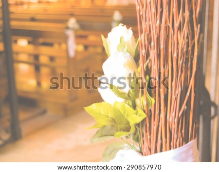 Beautiful white roses  wedding decoration in the church. Retro aged blurred dreamy image. - stock photo