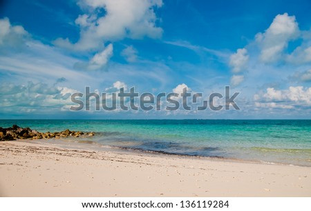 Beautiful white sand beach and blue ocean water on sunny day - stock photo
