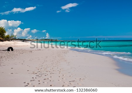 Beautiful white sand beach and turquoise waters and pretty blue sky.  islands of the bahamas.  tropical veiw of the ocean with puffy clouds in the sky.  copy space available - stock photo