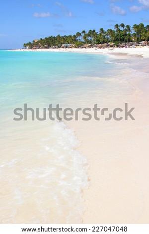 Beautiful white sand beach lined with palm trees with turquoise sea & blue sky, Aruba - stock photo