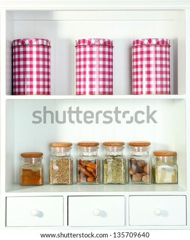Beautiful white shelves with spices in glass bottles - stock photo