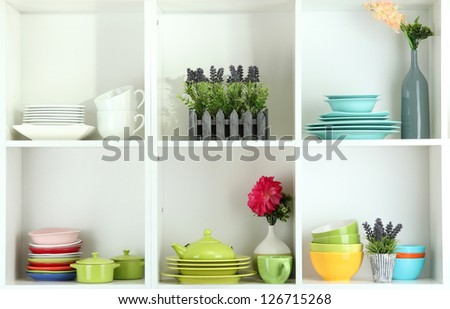Beautiful white shelves with tableware and decor - stock photo