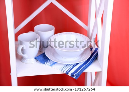 Beautiful white shelves with tableware and decor on color background
