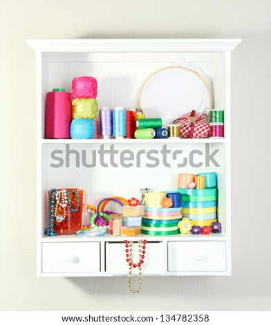 Beautiful white shelves with thread and material for handicrafts