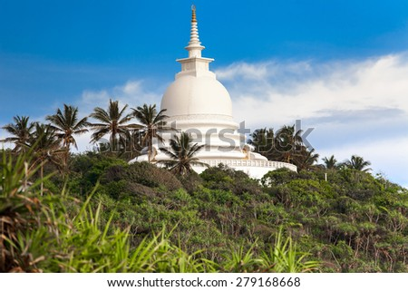 Beautiful white temple above green trees, Sri Lanka. - stock photo