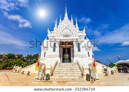 Beautiful white temple against bright blue sky in Thailand