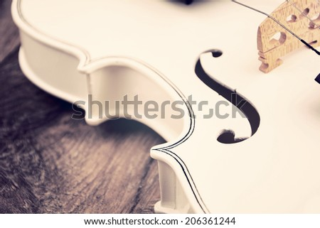 Beautiful white violin on the wooden table - stock photo