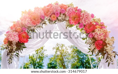 Beautiful white wedding arch decorated with pink and red flowers outdoors