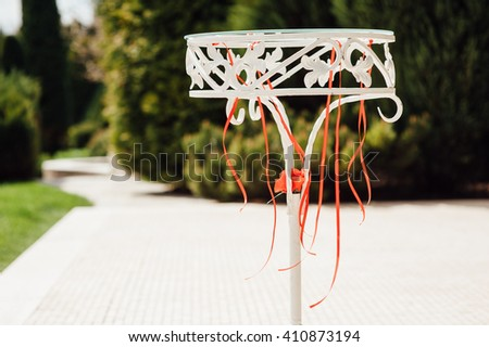 Beautiful white wedding arch decorated with pink and red flowers outdoors - stock photo
