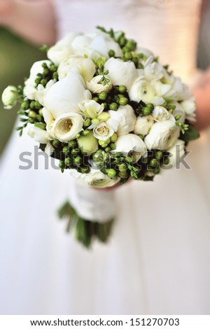 Beautiful white wedding bouquet in hand of bride