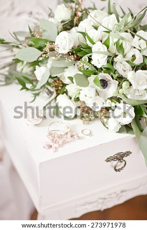 Beautiful white wedding bouquet on the white vintage bedside table - stock photo