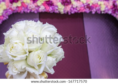 beautiful white wedding flowers bouquet with violet background at wedding ceremony