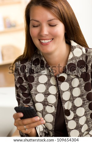 Beautiful white woman with brunette hair working in an office wearing a polka dot brown and white suit.