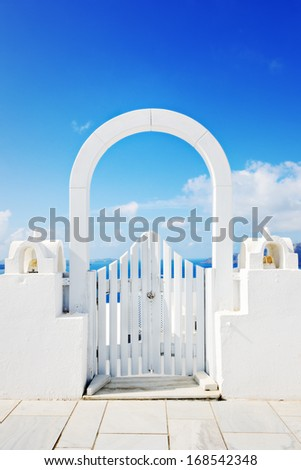 Beautiful white wooden door above aegean sea in Oia, Santorini, Cyclades, Greece