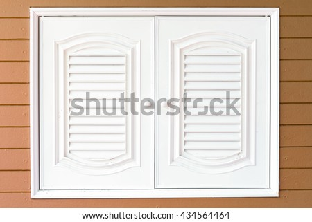 Beautiful white wooden door of modern cupboard on wooden background. - stock photo