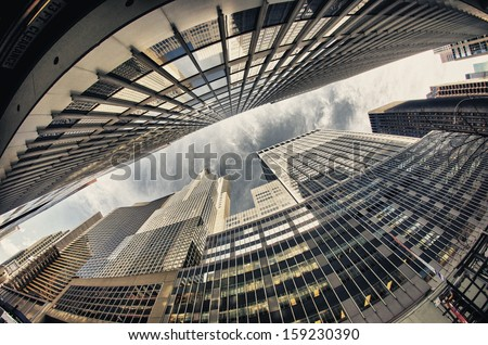 Beautiful wide angle upward view of Manhattan Skyscrapers from street level - New York City. - stock photo