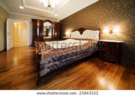 Beautiful wide bed in a modern bedroom - stock photo