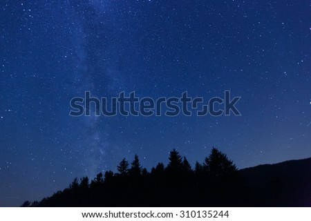 Beautiful, wide blue night sky with stars and visible Milky way galaxy, photographed on a mountain pasture. Astronomy, romantic, clear sky concept and background.  - stock photo
