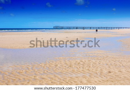 Beautiful wide open sandy beach over looking jetty pier in background. - stock photo