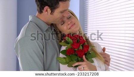 Beautiful wife gets surprised with bouqet of roses - stock photo