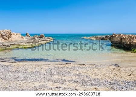 Beautiful wild beach with clear turquoise water and rocks. Malia, Crete island, Greece.  - stock photo