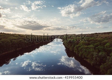 Beautiful wild nature park, forest. River or lake with mirror reflections and clear water on sunny day. Amazing wilderness nature landscape panorama. Quiet river in surroundings greenery in summer. - stock photo
