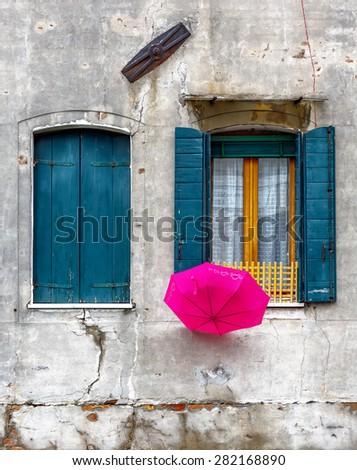 Beautiful window and umbrella on the ancient wall - Venice, Italy - stock photo