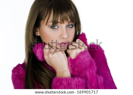 Beautiful winter girl in pink fur coat on white background