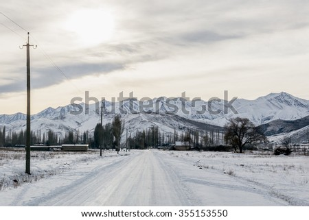 Beautiful winter landscape at dawn, an icy road leading towards the Tian-Shan mountain range, Kyrgyzstan. - stock photo