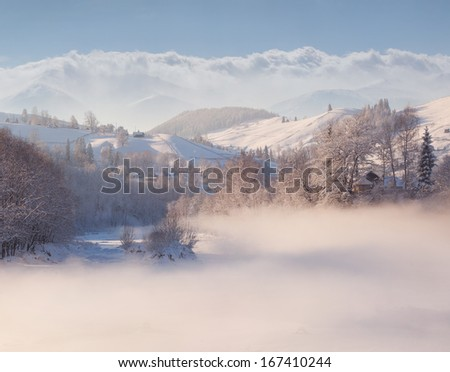 Beautiful winter landscape in the mountain village. Foggy morning
