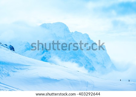 beautiful winter landscape of Dombaj with clouds and descent from the mountain - stock photo