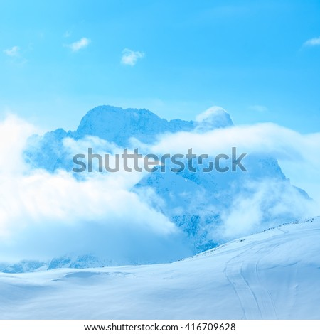 beautiful winter landscape of Dombaj with clouds and descent from the mountain, Russia  - stock photo