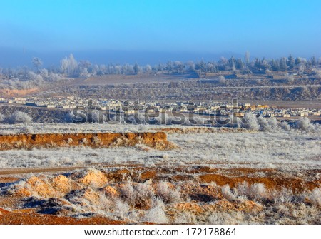 Beautiful winter landscape - small village and a field with frozen trees and grass against the background of blue misty sky near Goreme, Cappadocia, Central Anatolia, Turkey  - stock photo
