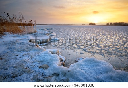 Beautiful winter landscape with frozen lake and sunset sky. Composition of nature. - stock photo